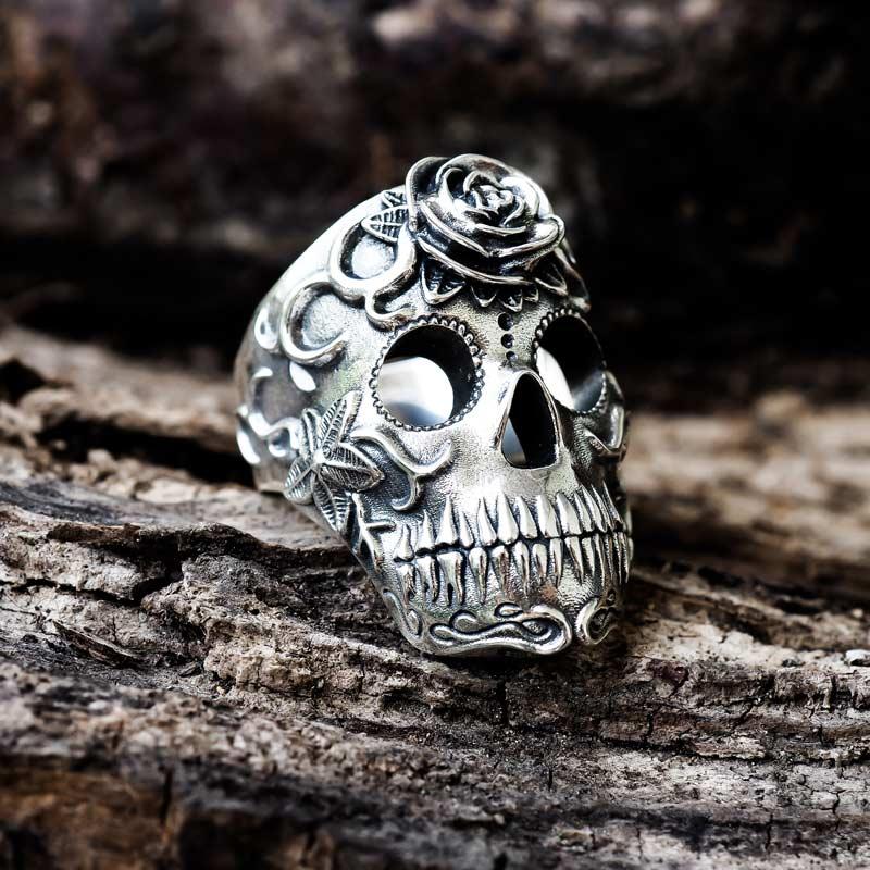 Anello teschio messicano los muertos in argento sopra ad una base di legno