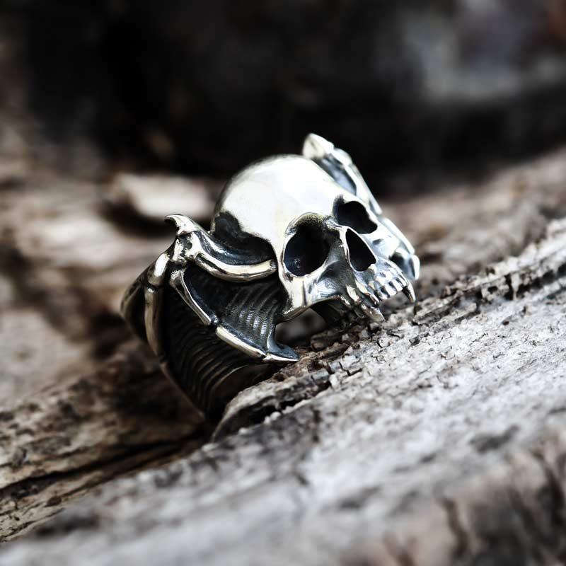 Anello teschio vampiro in argento su una base di legno