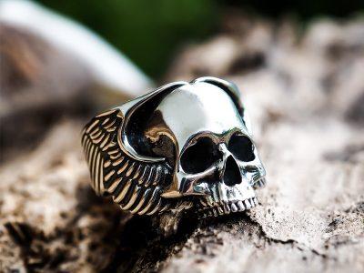 Anello teschio con ali d'angelo in argento su base di legno