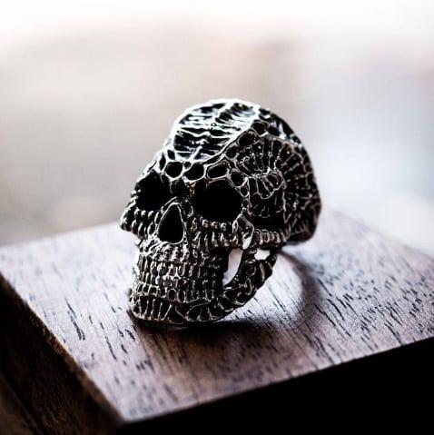 Anello teschio xeno in argento 925 su una base di legno