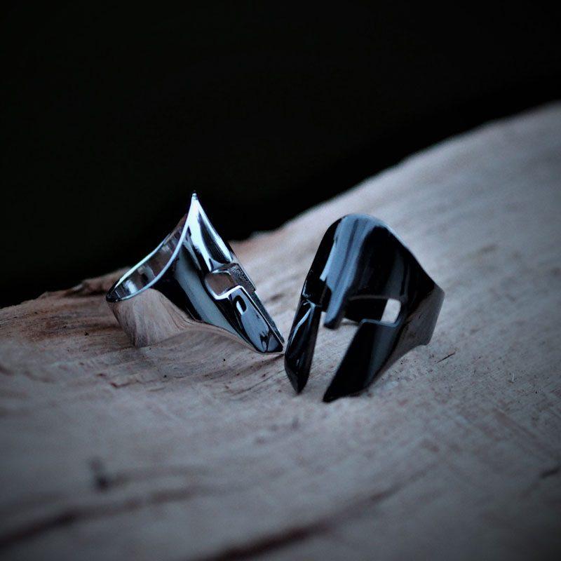 Anello elmo spartano in argento rodiato bianco e nero su una base di legno