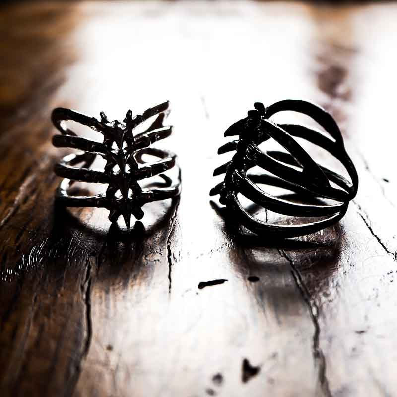 Rib Cage Ring in Silver 925 on a backlit wood table - Feel No Pain