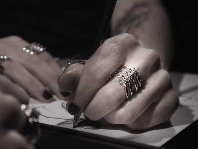 Anello scheletro coste in argento su dito medio e mano che scrive