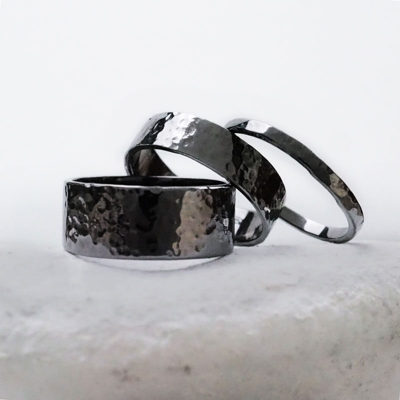Hephaestus rings with hammering and black galvanic treatment on white stone