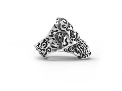 Anello teschio kamate in argento 925 con simbologia maori in vista laterale e sfondo bianco