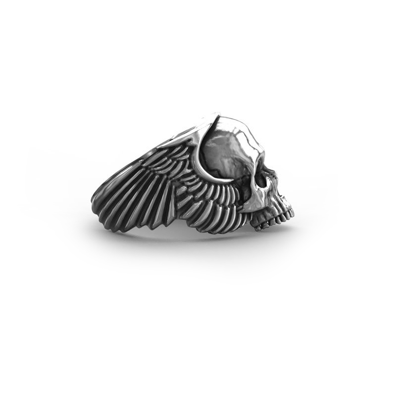 Anello teschio con ali d'angelo in argento in vista laterale con sfondo bianco