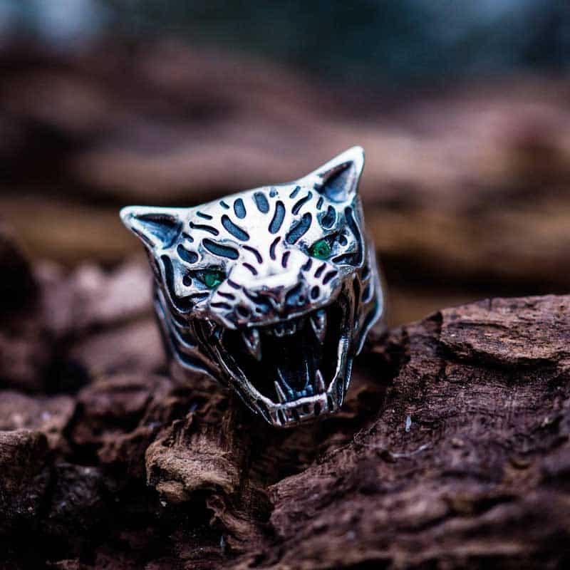 Anello tigre in argento 925 con zirconi verdi negli occhi su base di legno