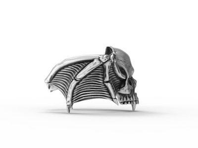 Anello teschio vampiro in argento in posizione laterale e sfondo bianco